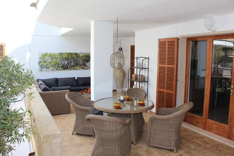 Überdachte Terrasse mit Esstisch und Couch