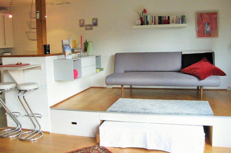 Das ausklappbare Sofa auf dem Podest