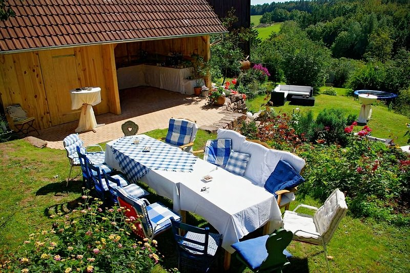 Sonniger Terrassengarten mit Grill, Trampolin, Sandkasten