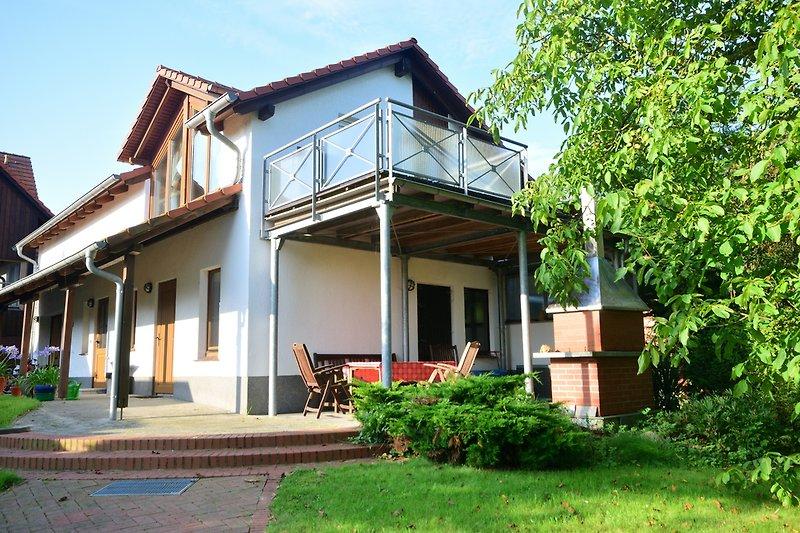 Hausansicht mit Balkon und überdachter Terrasse