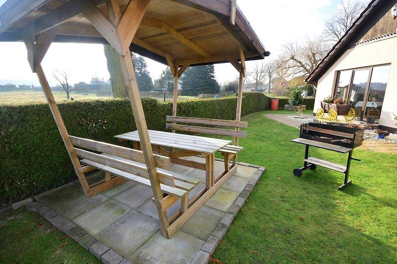 Überdachter Sitzbereich mit Grill im Garten