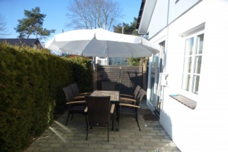 Terrasse mit Strandkorb, Terassenofen, Gartenmöbeln und Sonnenschirm