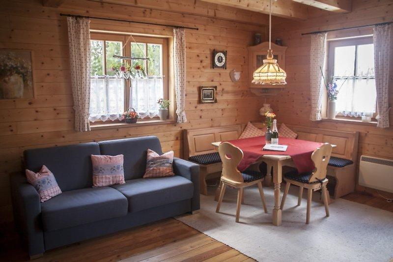 Wohnbereich mit Schlafsofa, Essecke, Fernseher, zwei gemütlichen Sesseln und Holzofen