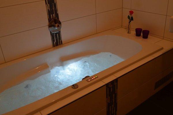 Badezimmer mit Whirlpool und Regendusche