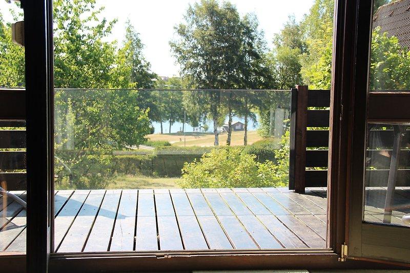 Blick vom Wohnzimmer durch das neue Glasbalkonelement zum Nageler See