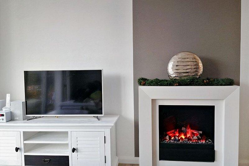 Fernseher und Kamin im Wohnzimmer WOOGEHUS