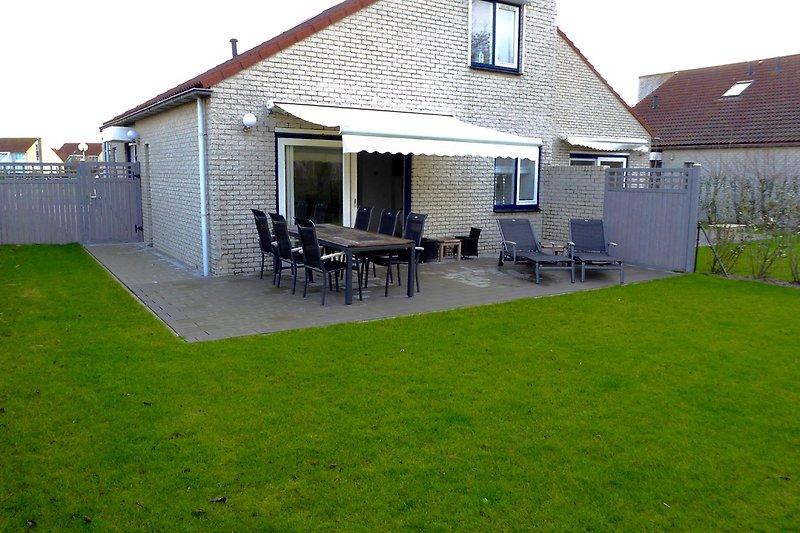 Terrasse in Südwestlage mit Gartenmöbeln und Markise, Kindermöbel