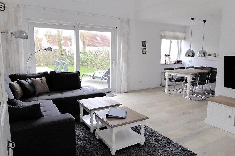 Blick in den Wohnraum mit Terrasse und Essplatz, Küche hinter dem Essplatz