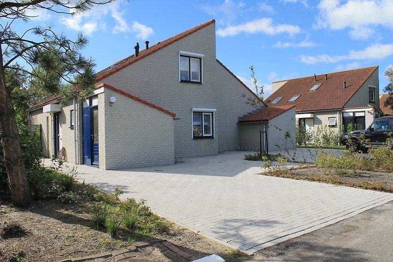 Hauseingang mit Abseite und Vorderseite mit Parkplatz und Fahrradständer