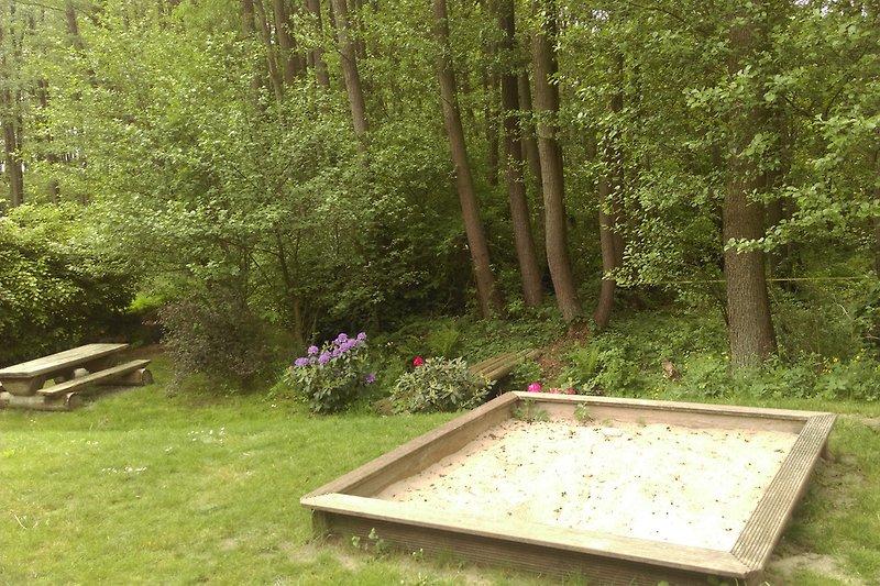 Sandkasten und Sitzgruppe am Bach hinterm Haus