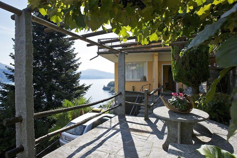 Ca. 20 m² große längliche Terrasse mit Steintisch und -bank sowie Weinpergola und zauberhafter Sicht auf den See
