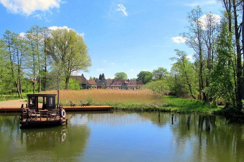 Blick vom See auf den Polly Ferienhof - am Steg hat ein Tante Polly Floß festgemacht