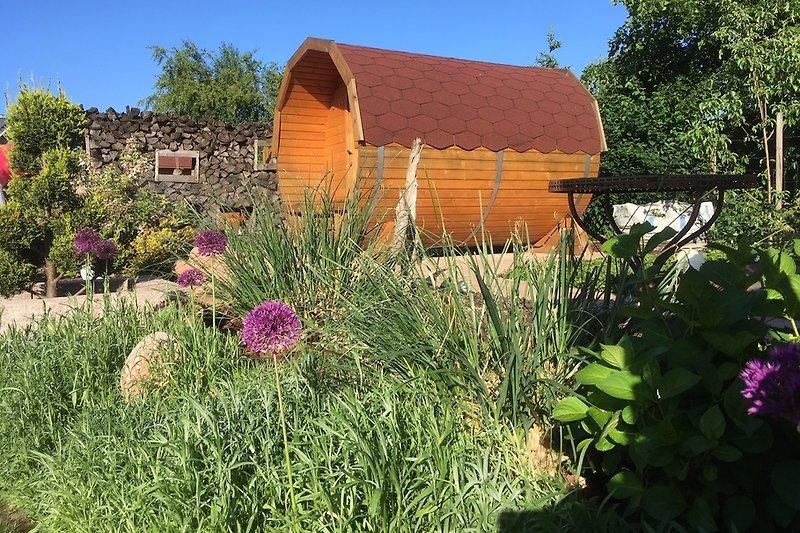 Blick in den Garten mit Saunafass