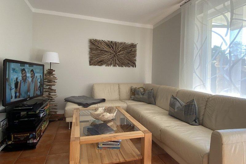 Im Wohnbereich mit mütlicher Couch, TV, Blue Ray Player und Sky Receiver