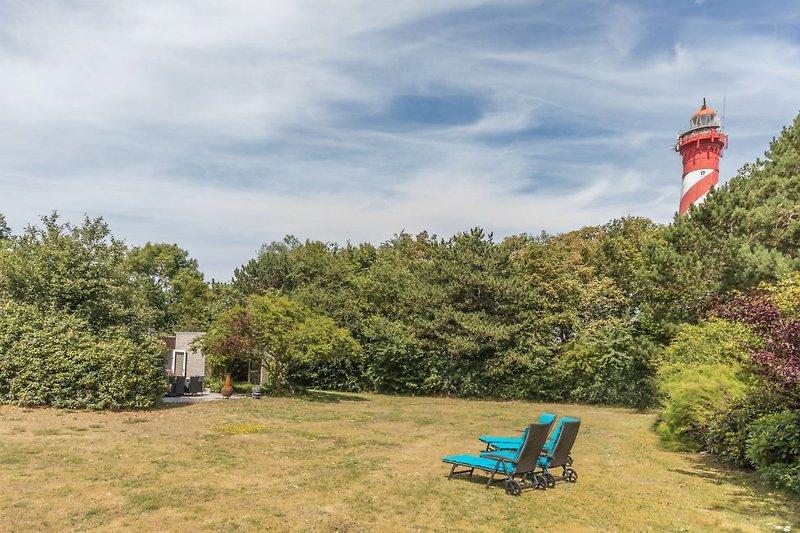 Der große, eingezäunte Garten mit Liegen und Lounge-Ecke, mit herrlichem Blick auf den Leuchtturm