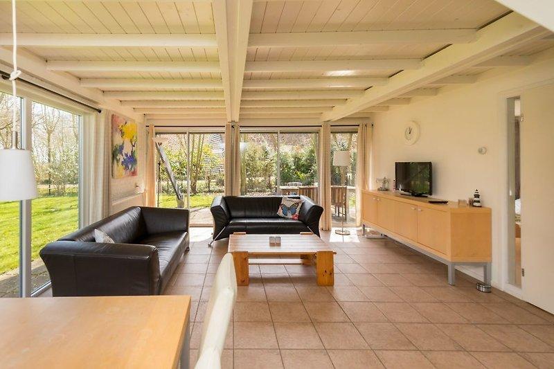 Das helle Wohnzimmer mit mehreren Schiebetüren