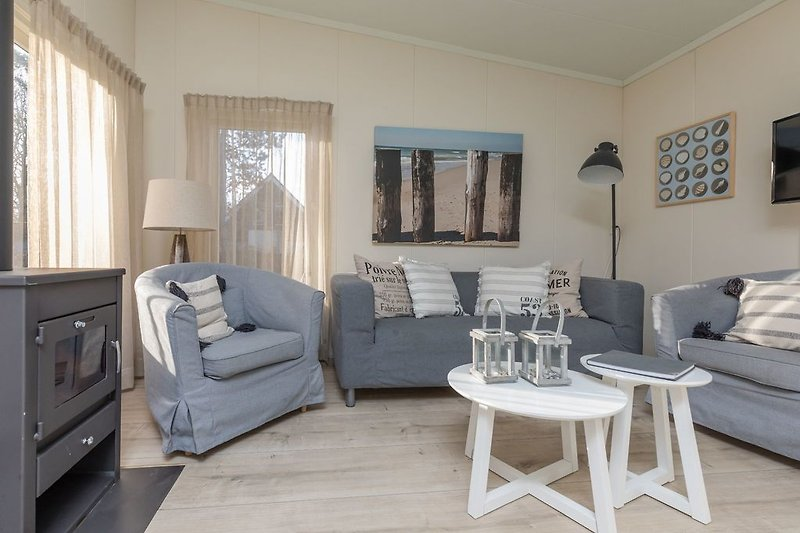 Das helle, gemütlich eingerichtete Wohnzimmer mit Kamin