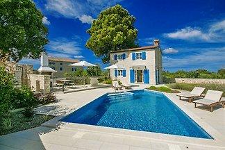 Neuerbaute Villa mit Pool und Hydromassageecke, Grillkamin, Tisch und Stühlen für Mahlzeiten im Freien und zwei überdachte Parkplätze.