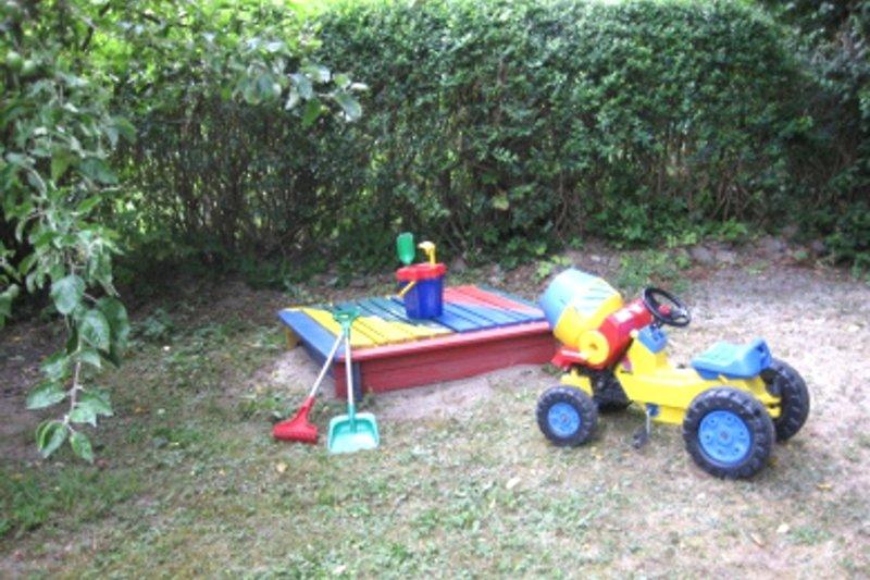 Ferienhaus in Blankensee in der Mecklenburger Seenplatte Blick auf den kleinen Sandkasten mit Spielzeug im Garten
