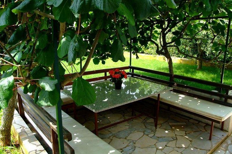 Terrasse mit Steintisch und Banke