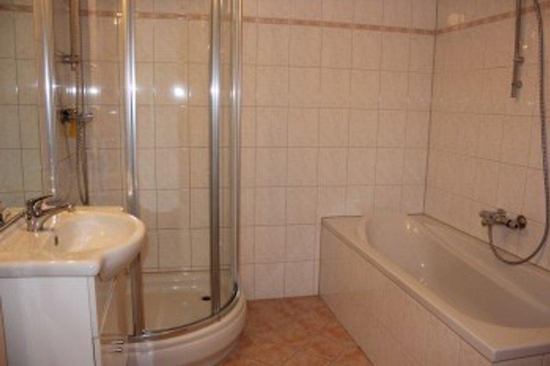 Badezimmer mit badwane, Dusche und Toilet. Daneben noch ein separate Toilet