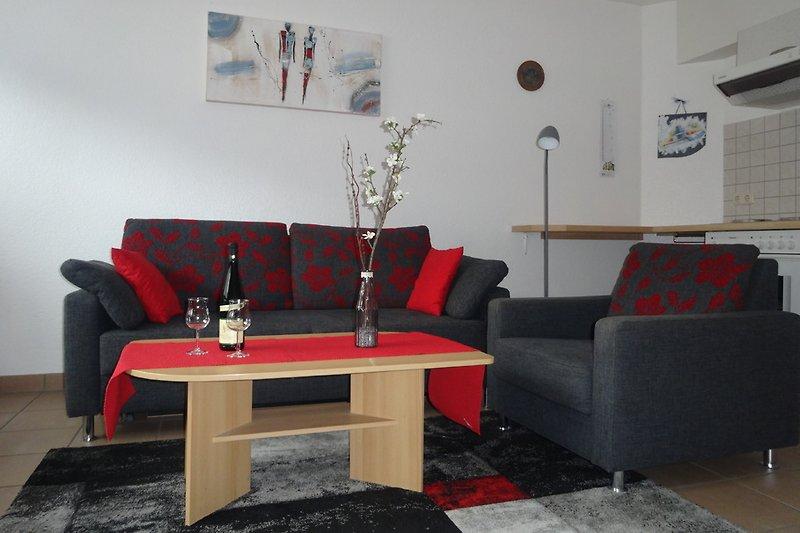 Heller Wohnraum, moderne Schlafcouch mit Flachbildfernseher und LED-Stehleuchte