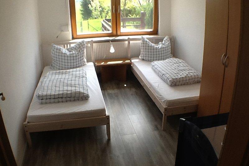 Schlafzimmer mit 2 Einzelbetten und 1 Babybett