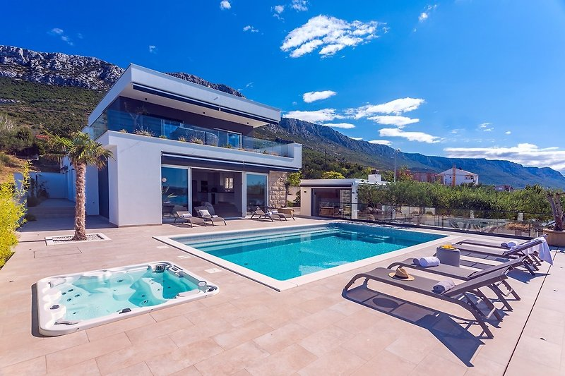 The outdoor area offers a heated private pool, jacuzzi, and a huge sun deck