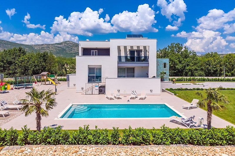 Private, heated pool with spacious sun deck in front of the villa with 10 sun chairs