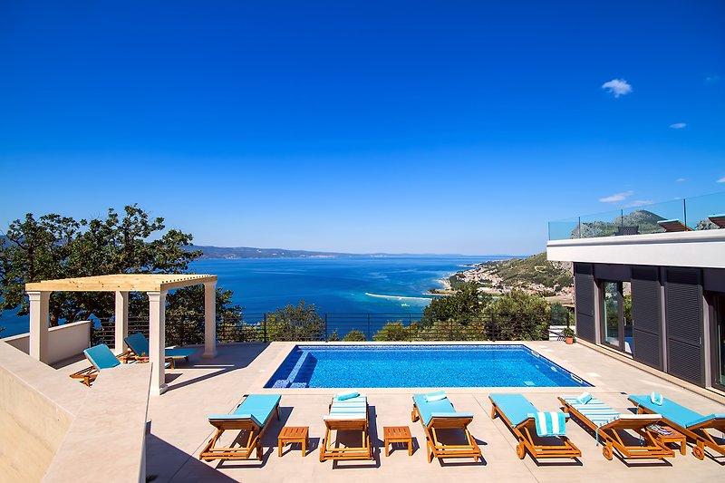 32 m² großer Pool mit Massage, Sonnenterrasse mit 8 Liegen und offenem Meer- und Küstenblick