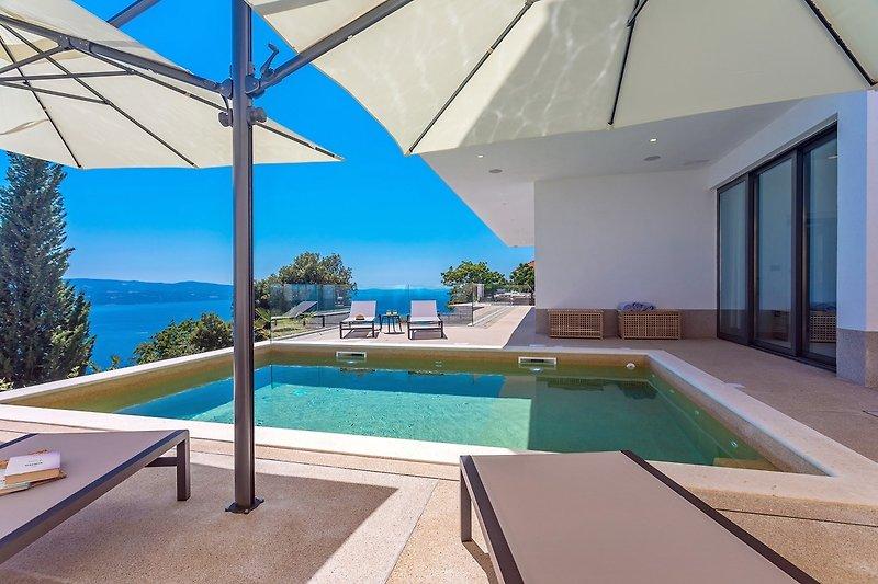 Der Außenbereich bietet einen privaten, beheizten 24 m² großen Pool mit Hydromassage