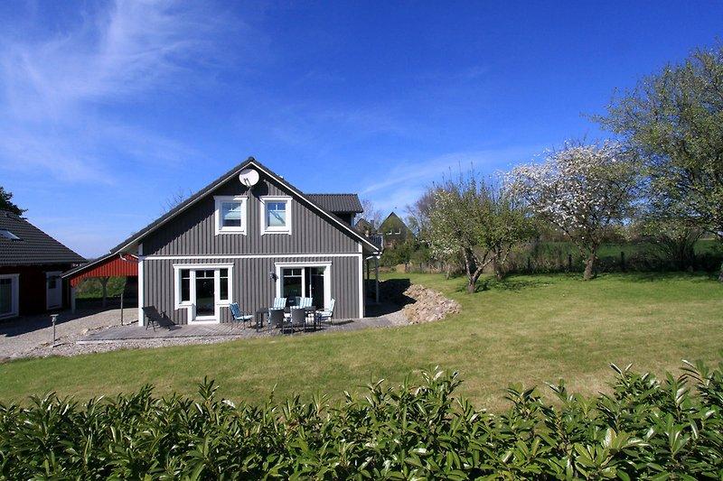 Skandinavisches Haus mit Garten, Strandkörben und Gartenmöbeln