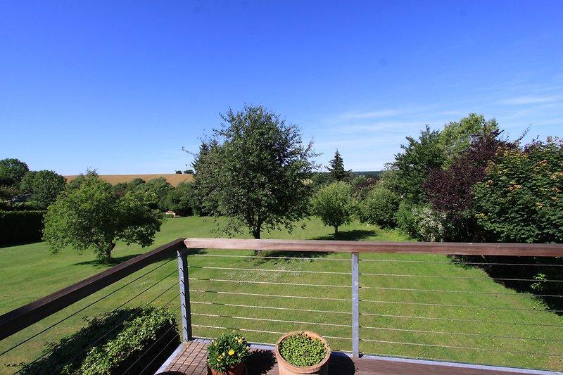 Weitblick vom Balkon mit Gartenmöbeln und Grill