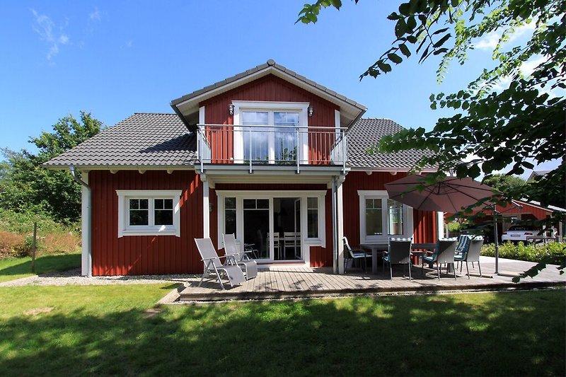 Skandinavisches Holzhaus mit Terrasse, Balkon und Garten