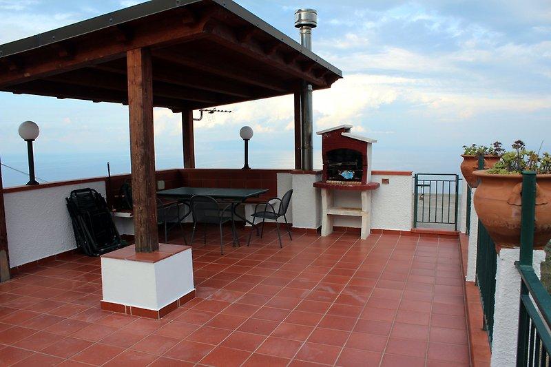 Die Dachterrasse mit Sitzgelegenheiten, Teilüberdachung, Grill sowie Liegestühlen