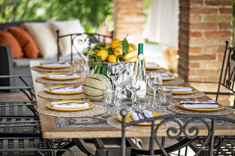 Villa Amata - Veranda mit Tisch, Stühlen und Sitzecke