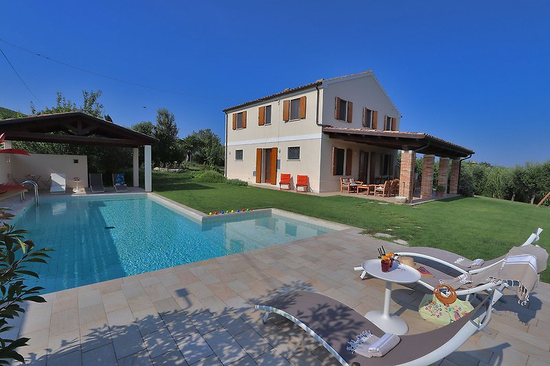 Casale San Basso - View of the house and pool area with porch to relax