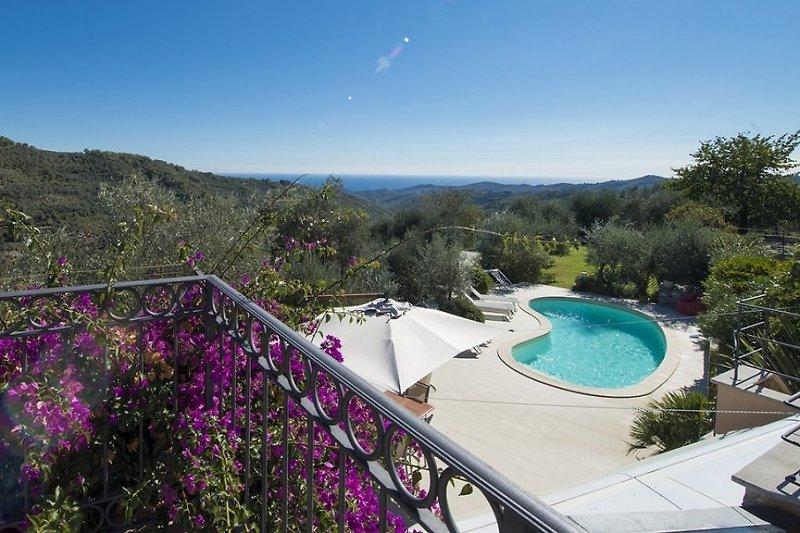 Der wunderschöne Blick von einer der Dachterrasse hinunter zum Pool. Im Hintergrund das Mittelmeer.