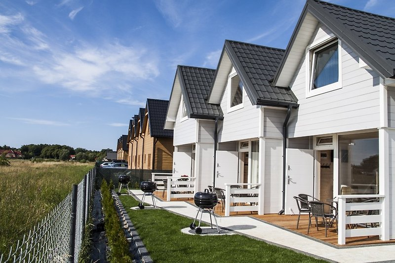 Wooden, holiday homes with terraces and individual barbecue area.