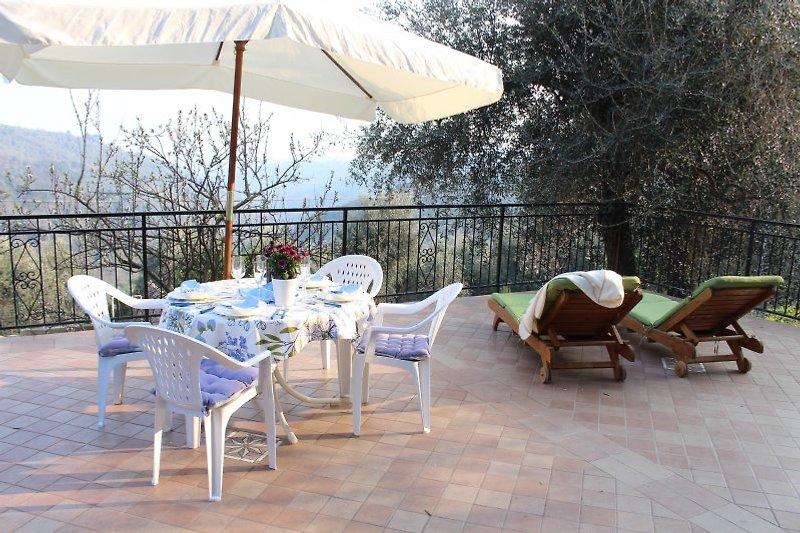 Von der Terrasse führt eine Treppe hinuter in den kleinen Garten mit Außendusche.