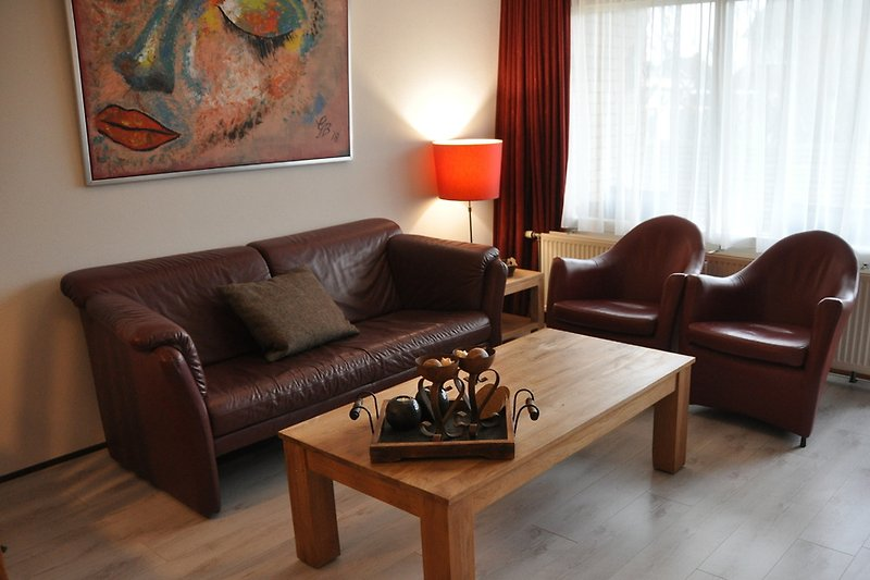 Wohnzimmer mit Ledercouch und Stühlen