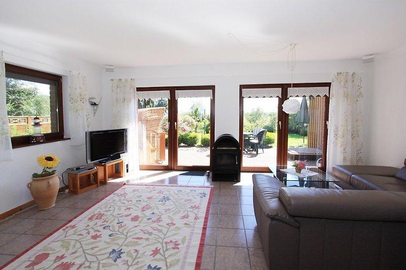 Wohnzimmer mit Kamin und Terasse