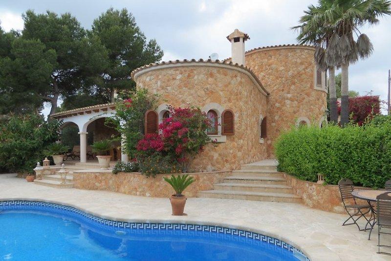 Traumhafte Finca mit herrlicher Gartenanlage vom großen Pool aus gesehen.
