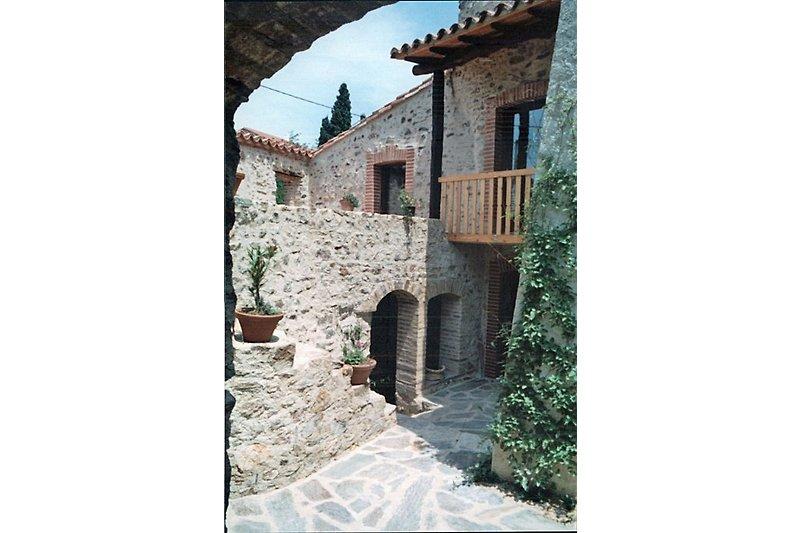 """Der Blick vom Hof: Links der Aufgang zur Terrasse, über den Balkon rechts kommt man ins """"Kaminzimmer"""""""