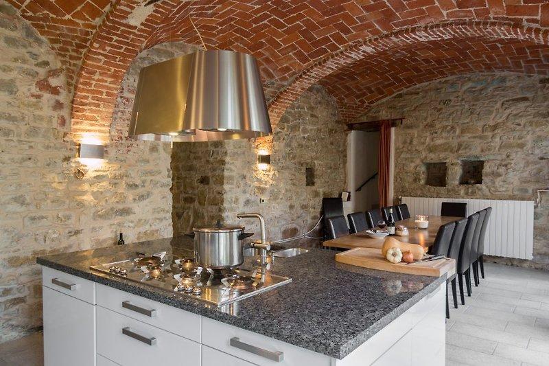 Wohnküche unter Kreuzgewölbe mit Kochinsel und langem Esstisch