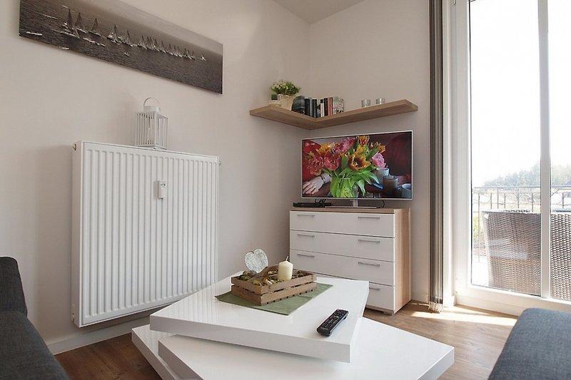 Wohnbereich mit Flatscreen-TV und Balkonzugang