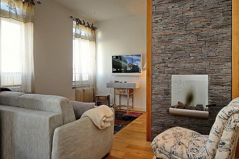 Wohnbereich mit Sofa, Flachblid-TV, Bioethanol Kamin und Sessel