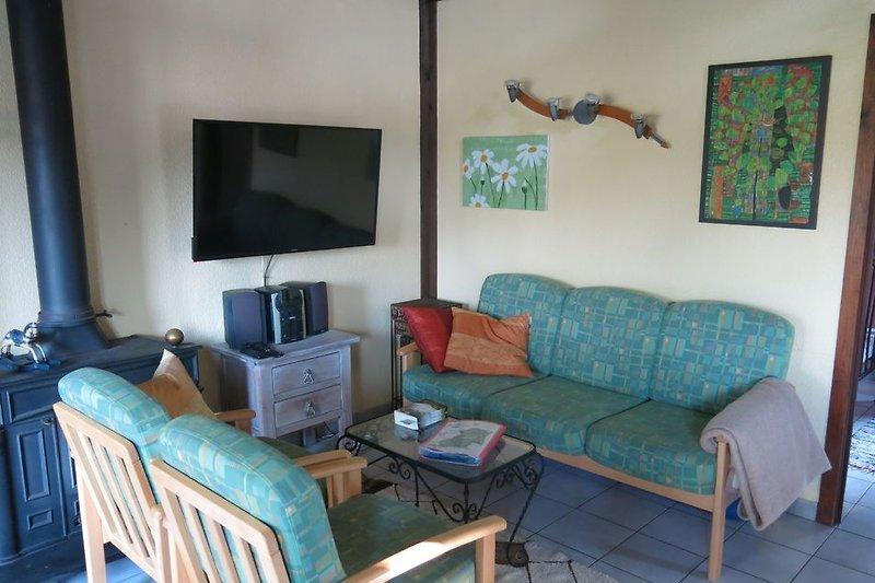 Wohnzimmer mit großem Fernseher und Kamin