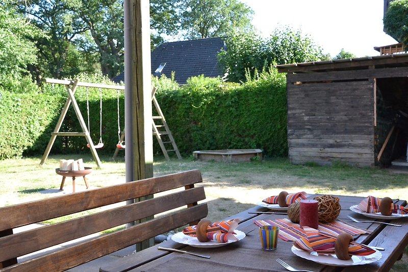 Terasse mit Spielplatz und Holzmiete