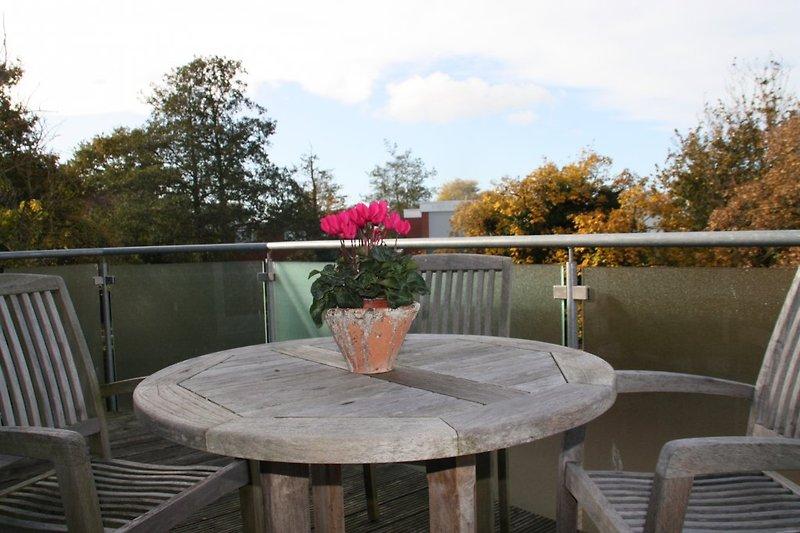 Sonnenbalkon - mit Teakmöbeln möbliert für eine Mahlzeit im Freien.